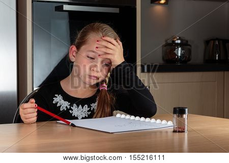 Girl thinking while doing her homework and holding a pencil