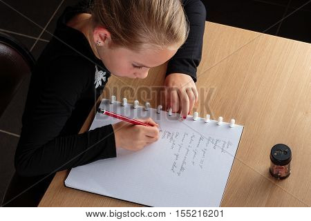 Young girl doing homework at home at the kitchen table.