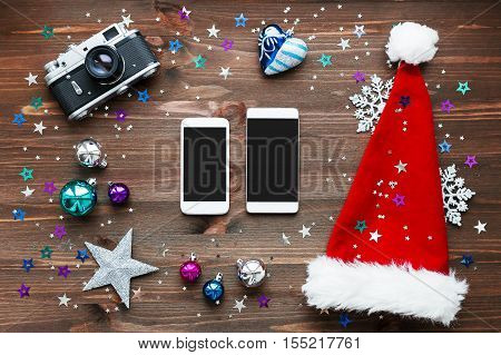 Christmas and New Year background with two smartphones old fashioned camera red Santa's hat decorations - balls stars silver sparkling snowflakes confetti on wooden table. Mock up place for your text.