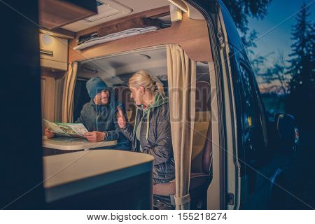 Couples and the RV Park Camping. Young Couples Planning Next Trip in the Motorhome.