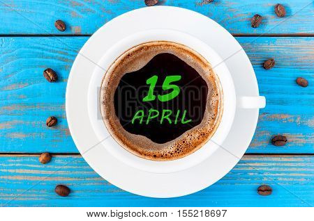 April 15th. Day 15 of month, calendar written on morning coffee cup at blue wooden background. Spring time, Top view.