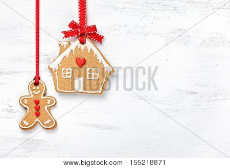 Hanging Gingerbread Man and House Cookies over a white background