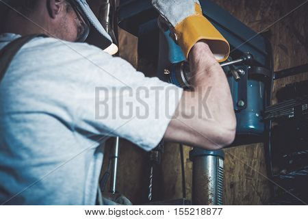 Garage Metal Works. Men and the Professional Grade Driller in His Garage.