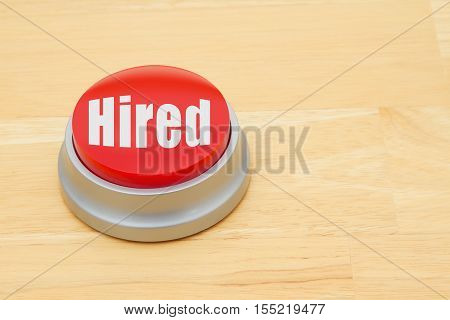 A Hired red push button A red and silver push button on a wooden desk with text Hired