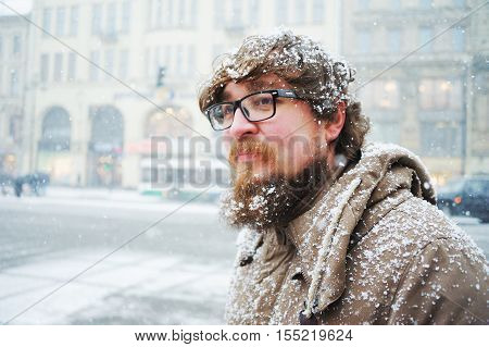 Reckless Russian bearded guy in glasses without a hat covered with snow walking in the center of St. Petersburg during a Blizzard on a cold winter day