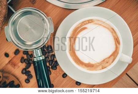 Tasty Italian Cappuccino and the Professional Portafilter on Wooden Table. Top View Photo. Coffee Cappuccino Cup.