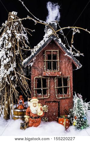 arts and craft still life of Santa and his dog in deep snow leaving gifts at rustic home