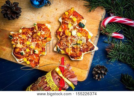 Funny Christmas meal for children: pizza in the form of Christmas trees, vegetables and cheese.