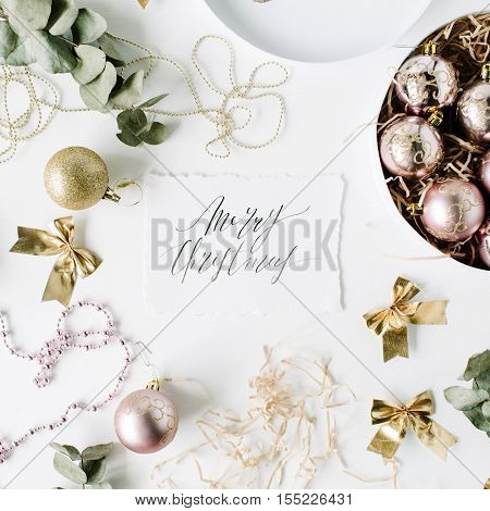 calligraphy words merry christmas and frame made of christmas decoration with christmas balls tinsel bow eucalyptus. christmas wallpaper. flat lay top view