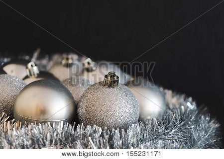 Modern vintage high contrast photo of shiny bright silver christmas balls decoration lying on silver christmas chain on dark backdrop in soft focus.
