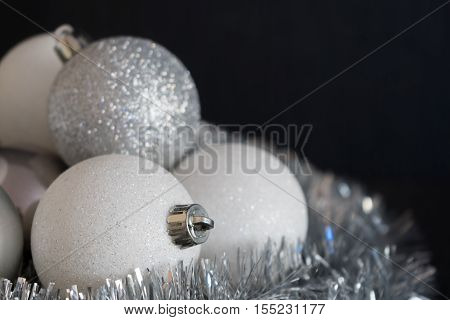 Shiny and bright white christmas balls decoration lying on silver christmas chain on dark black structured background. Decoration detail in soft focus.