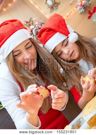 Portrait of a loving mother teaching her little daughter to make homemade sweets, baking ginger bread and Christmas cookies together