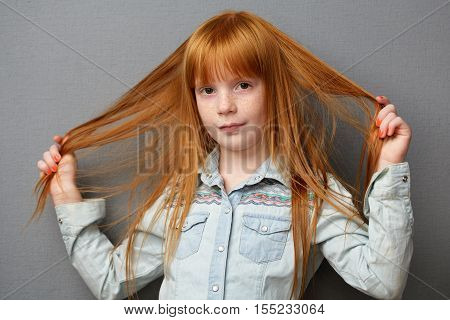 Cute ginger girl with beautiful red hair gray background
