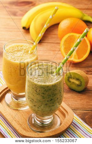 Healthy orange and kiwi smoothies with banana on brown wooden background.