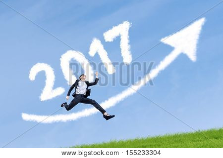 Attractive female entrepreneur leaping in the meadow with clouds shaped numbers 2017 and upward arrow