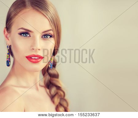 Beautiful  brunette model girl with  long braid hair . Hairstyle  pigtail  . Orange lips and jewelry earrings .