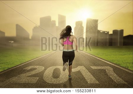 Back view of healthy woman wearing sportswear and running on the road with number 2017 toward the city