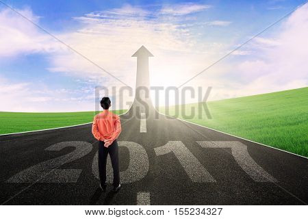 Rear view of a businessman standing on the street with number 2017 and looking at upward arrow