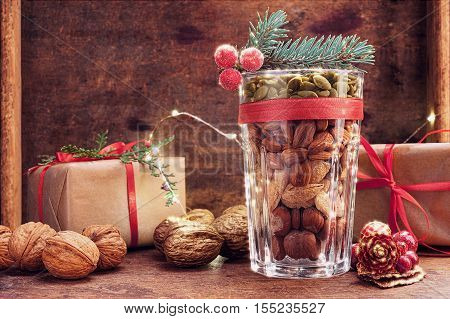 Christmas decoration glass with a variety of nuts on a wooden background with copy space