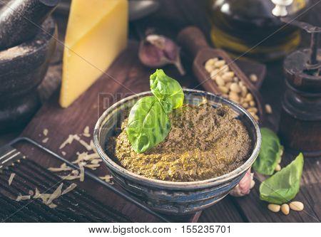 Bowl of fresh italian basil pesto and ingredients