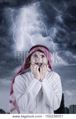 Image of Arabian businessman looks scared with lightning on the cloudy sky