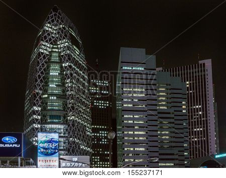 Tokyo Japan - September 29 2016: Night photo of the cocoon building the Tokyo Mode Gakuen adjacent to L-building. Plenty of lights and a few large neon signs. Black sky.