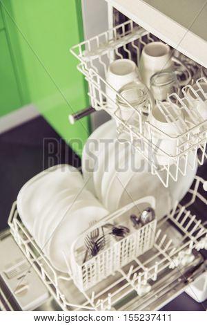 Modern open dishwashing machine with dishes in kitchen