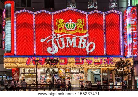Tokyo Japan - September 29 2016: Night photo of the Jumbo Pachinko hall near Shinjuku station. Red wall of neon signs people and black sky.