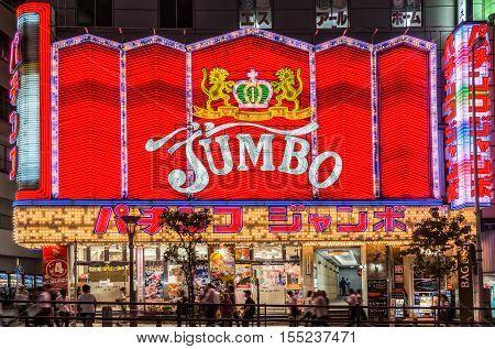 Tokyo Japan - September 29 2016: Night photo of the Jumbo Pachinko hall near Shinjuku station. Red wall of neon signs people and black sky.