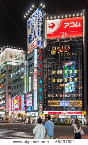 Tokyo Japan - September 29 2016: Night photo of a corner at an intersection near Shinjuku Station. Plenty of bright neon signs with Roman and Japanese characters. Reflections lights people and black sky.