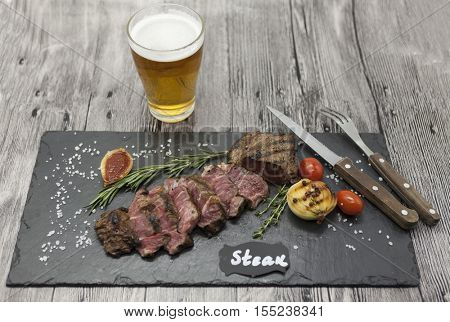 Grilled striploin steak on a stone plate with a glass of beer with a fork and knife