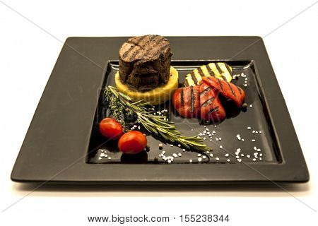 Mignon steak with fried potatoes and grilled vegetables on a beautiful black plate on a white background