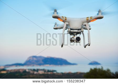 uav drone with high resolution digital camera flying in the blue sky over sea island