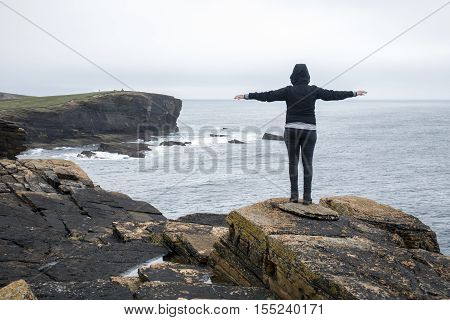 Girl looking Panorama of Orkney coastline Yesnaby cliff landscape