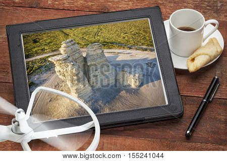 aerial photography concept - reviewing aerial pictures of the Castle Rock landmark in Kansas on a digital tablet with a drone rotor and coffee, screen picture copyright by the photographer