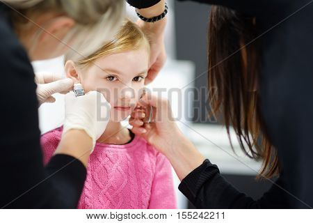 Adorable Little Girl Having Ear Piercing Process In Beauty Center