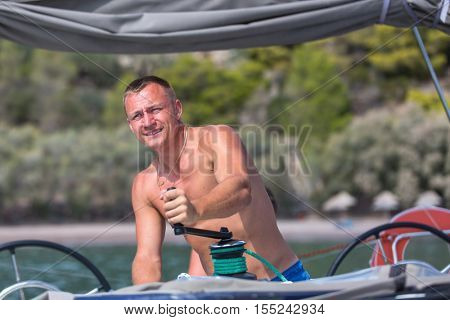 Sailing, man pulling ropes, winding sheets around winches. Luxery yacht boat.