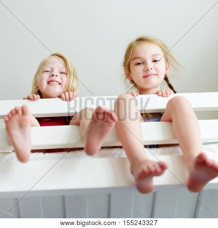Two Little Sisters Fooling Around, Playing And Having Fun In Twin Bunk Bed