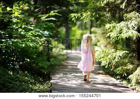Little Girl Wearing Pink Dress Taking A Walk All Alone