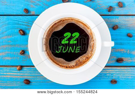 June 22nd. Day 22 of month, everyday calendar written on morning coffee cup at blue wooden background. Summer concept, Top view.