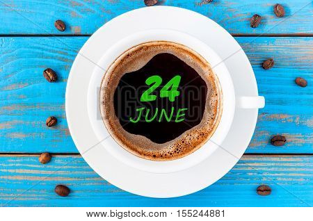 June 24th. Day 24 of month, everyday calendar written on morning coffee cup at blue wooden background. Summer concept, Top view.