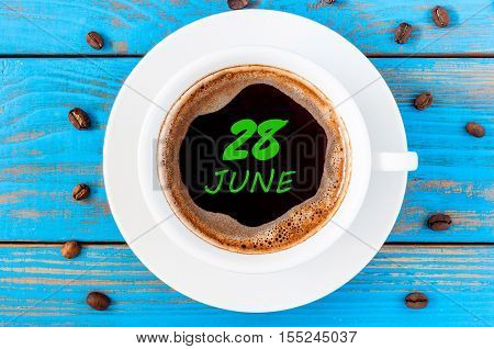 June 28th. Day 28 of month, everyday calendar written on morning coffee cup at blue wooden background. Summer concept, Top view.