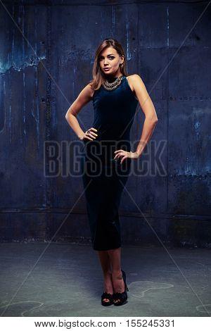Mid full-length portrait of stylish gorgeous brunette wearing eveningwear; posing over dark blue background. Holding hands on hips