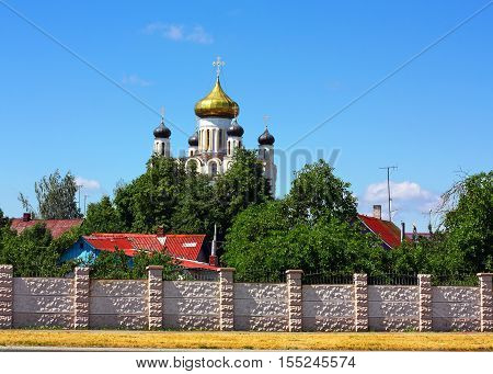 One-storeyed wooden houses with colored roofes on rhe background of church