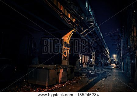 Dark Urban Alley at Night with Elevated Train