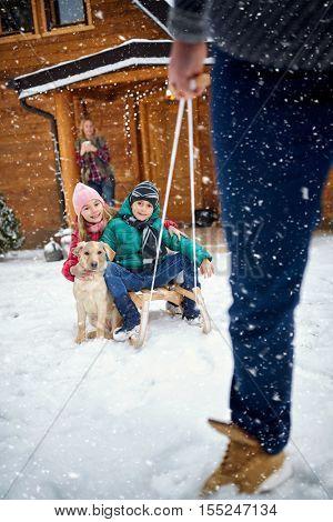 Winter, snow, family sledding at winter time- Family enjoying