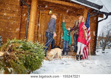 Happy family with Christmas tree on snowy day enjoying