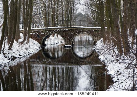 Foot arch bridge and its reflection in river at snowy winter weather.