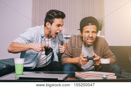 Two guys playing on the console sitting on the couch. European and African friends had a party. victory celebration