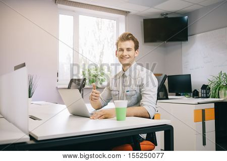Young worker sitting in an office at the computer. Freelancer in a white shirt. The designer sits in front of a window in the workplace. Office worker looking at the camera